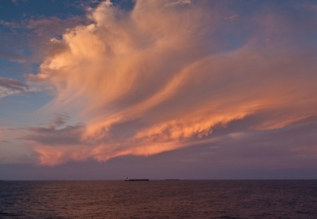 Brilliant copper coloured clouds at sea reflecting into the ocean with a ship on the horizon