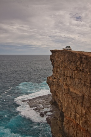 Portrait view of a vertical cliff face rising out of a turbulent ocean against a stormy sky  A 4WD vehicle is parked on the top of the cliff in an unusual position  Stock Photo