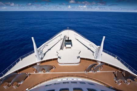 ship bow: View over the bows of a luxury cruise ship steaming in mid ocean under blue sunny sky, travel and vacation concept Stock Photo