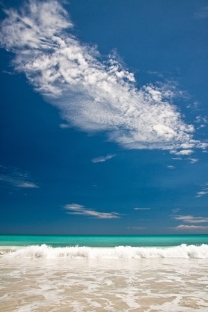 Portrait view of turquoise blue sea with breaking wave with a brilliant blue sky featuring a white textured cloud
