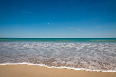 Landscape view of small breaking wave on beach with foam on the sand, against a calm sea and a bright blue sky  Stock Photo