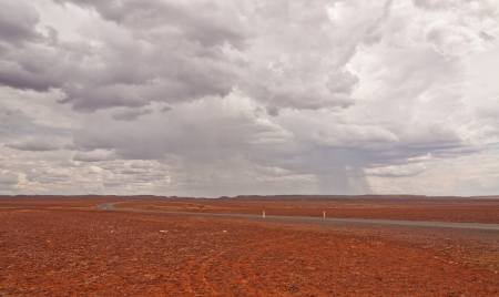 A landscape view of a road on a stony red  desert  disapearing into the horizon against a background of a dramatic stormy sky  Stock Photo