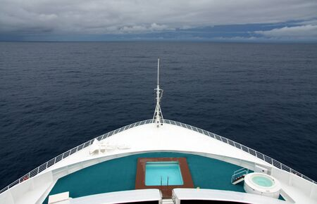 Landscape view of bow of large cruise ship heading into a large tropical storm on a leaden sea