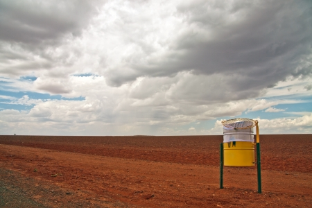 A landscape view of a bright yellow roadside rubbish bin in a red stony desert against a threatening cloudy sky