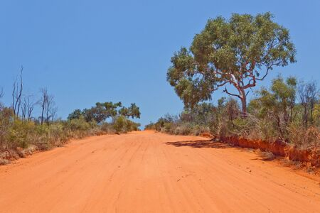 Red sandy outback road in the Australian desert against a brilliant clear blue sky  Stock Photo