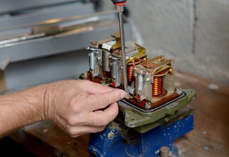 dynamo: Electrician repairs a regulator of car in his workshop Stock Photo