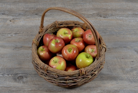 basket of apples on wood table Фото со стока