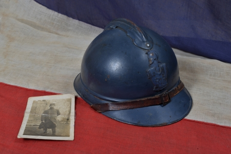 french ww1 helmet on the french flag with a soldier photograph