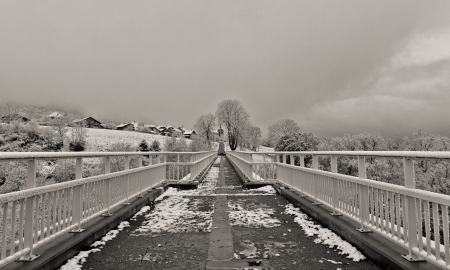 Access to the village under the snow in black and white photo