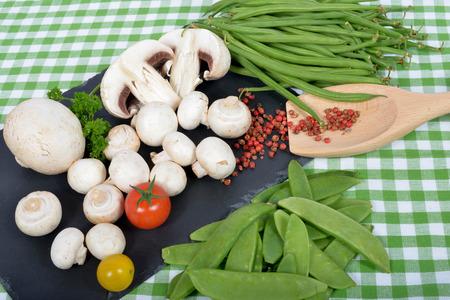 mycelium: Paris mushrooms on a slate plate with peas and beans Stock Photo