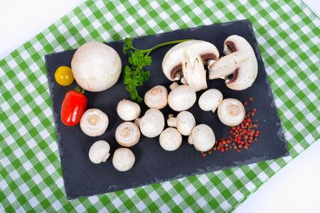mycelium: Paris mushrooms on a slate plate with tomatoes