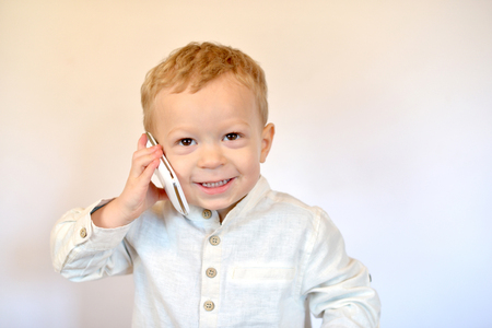 baby dressed in white smile with a mobile phore photo