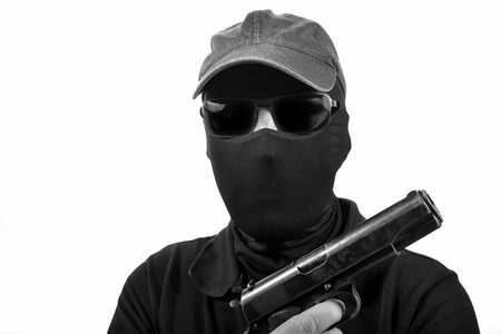 bezel: hooded man with a gun in black and white Stock Photo