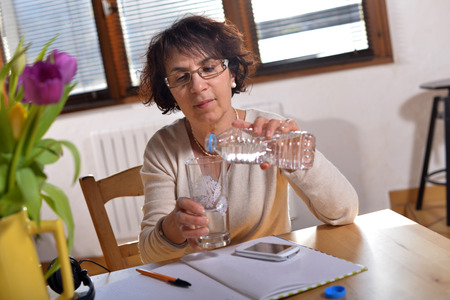 refreshed: woman at office refreshed with a glass of water