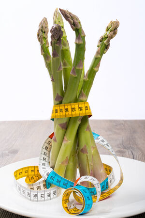 Bunch of raw asparagus linked up with a measuring tape photo
