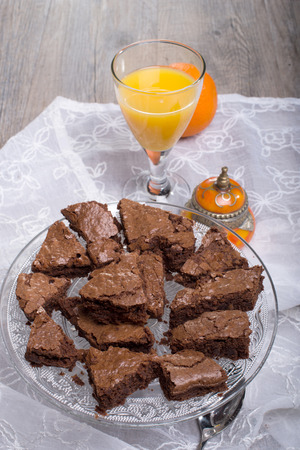 Un lote de brownies con un vaso de jugo de naranja photo