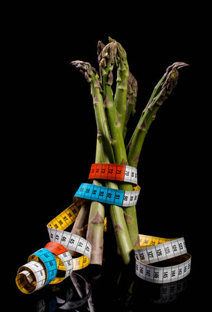 A small bunch of raw asparagus tied with a measuring ribbon isolated on a black background photo
