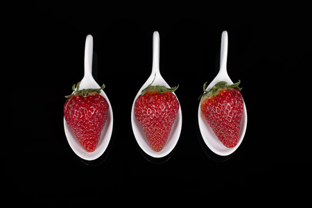 faience: three strawberries in faience spoons placed on a glass plate