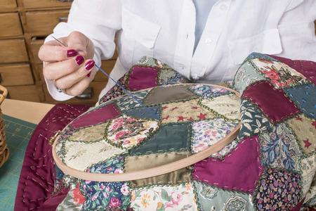 Rijpe vrouw door naaien en quilten in haar huis