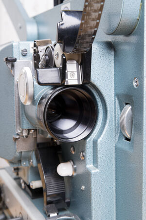 cinematographer: close up on the lens of a 16 mm film projector
