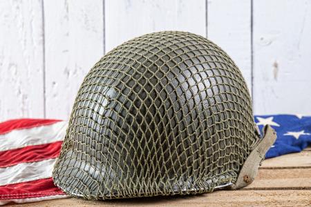 world war two: World War Two military helmet on an American Flag