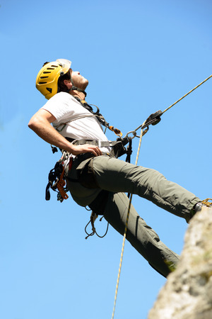 steeplejack: steeplejack climbing a rock wall with his equipment
