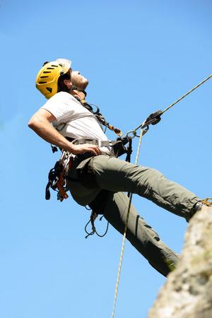 steeplejack: steeplejack climbing a rock wall with his equipment