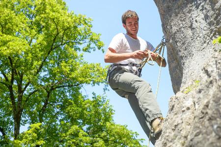 abseiling: young man climbing a rock wall