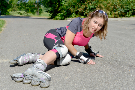 young woman dressed in pink fell on skates