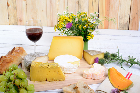 assortment of french cheeses and seasonal fruits photo