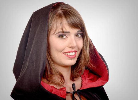smiling girl dressed in a black cape for halloween photo