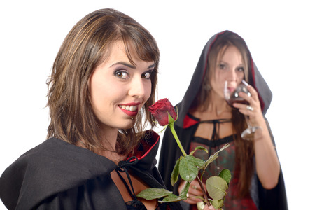 two young women in disguise halloween with a glass of blood and a rose  photo