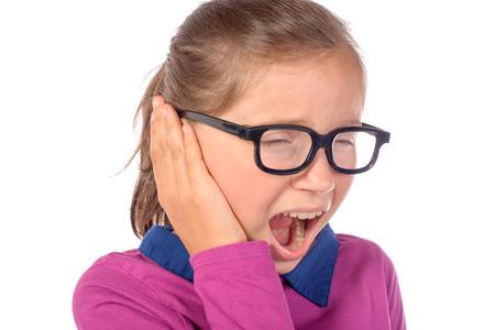 dolor de oido: niña un dolor de oído en el fondo blanco Foto de archivo