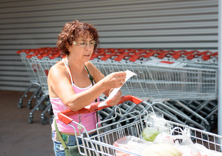 woman pushing a shopping caddy on parking of supermarket Foto de archivo