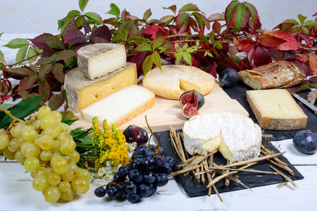 cheese platter: French cheeses with white and black grapes Stock Photo
