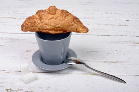 cup of coffee with a croissant photo