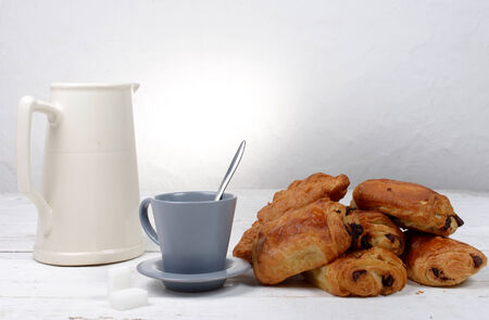 chocolate croissant on a white table with coffee photo