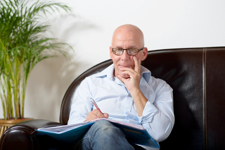 a senior man sitting in a sofa taking notes photo