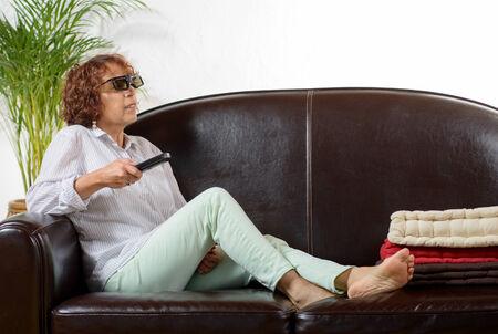 ver television: una mujer de edad madura ver la televisi�n con gafas 3D