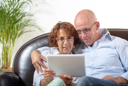 a senior couple watching a digital tablet photo
