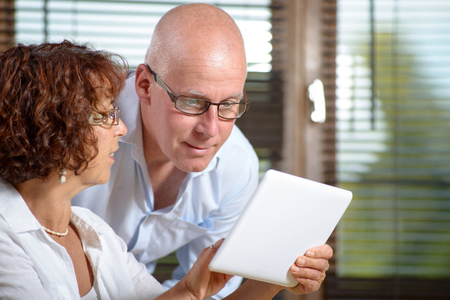 silver surfer: a senior couple watching a digital tablet
