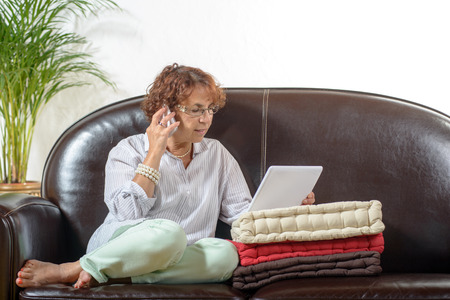 a senior woman in a sofa with a phone photo