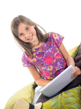 a little girl plays with her digital tablet in her bedroom photo