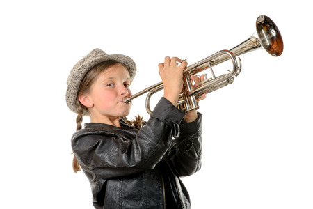 wind instrument: a pretty little girl with a black jacket and hat plays the trumpet Stock Photo