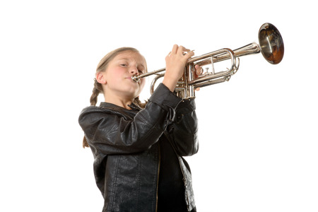 wind instrument: a pretty little girl with a black jacket plays the trumpet on white background Stock Photo