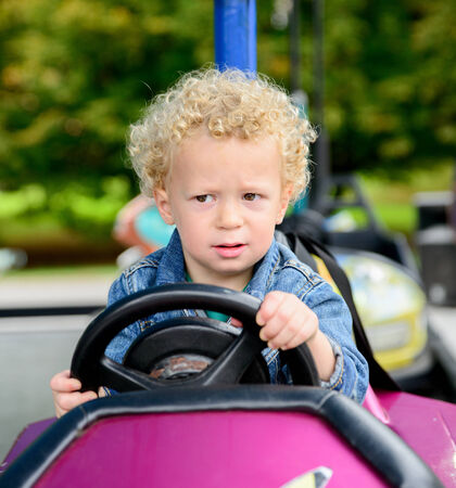 a little boy driving a bumper car at the carnival photo