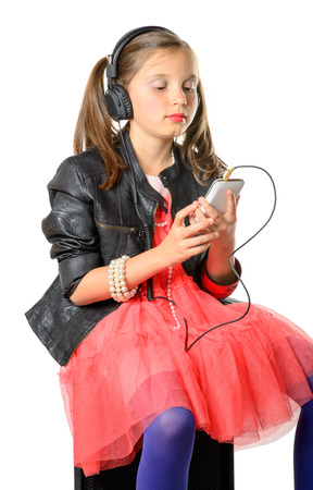 a young girl listening to music on his phone and headphones photo