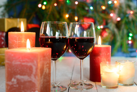 candle light dinner: glasses of red wine with Christmas decoration