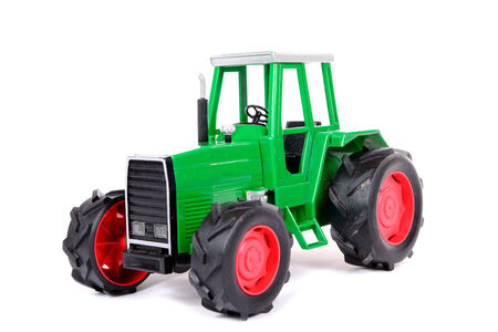 agricultural engineering: green toy farm tractor on the white background
