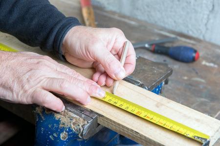 carpenter measuring a wooden board with pencil photo